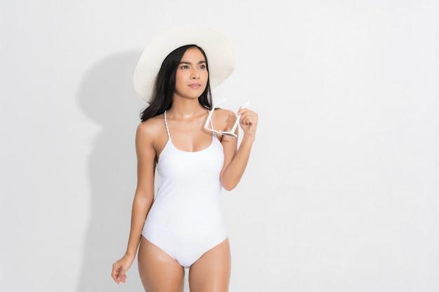 Piękna kobieta w szczęściu na sobie białą sukienkę strój kąpielowy i trzymając białe okulary post w koncepcji lato studio mody strzelać na białym tle.