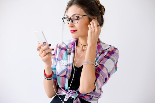 Piękna kobieta w szkłach cieszy się muzykę