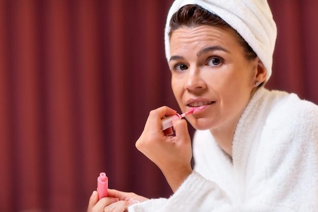 Piękna kobieta w szlafrok z ręcznikiem w głowie stosowania szminki
