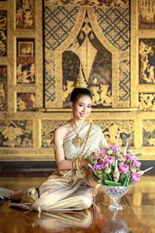Piękna kobieta w tajskim stroju ludowym w okresie ayuthaya siedziała na sznurku girland. i pięknie się uśmiechaj