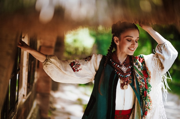 Piękna kobieta w tradycyjnej ukraińskiej sukni uśmiecha się