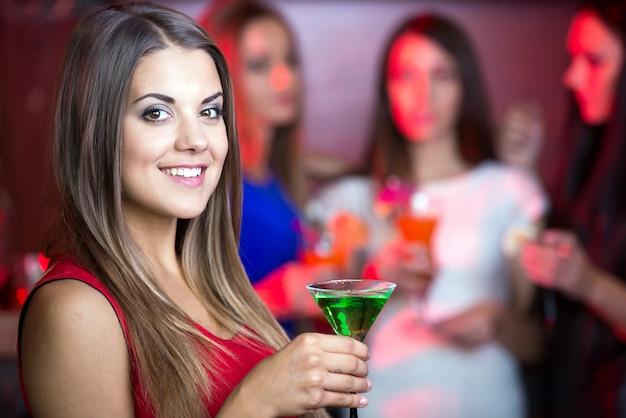 Piękna kobieta w wieczór sukni z koktajlami.