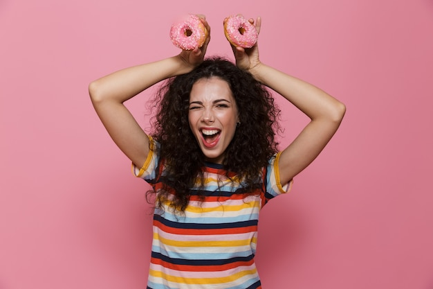 Piękna kobieta w wieku 20 lat z kręconymi włosami bawi się i trzyma pączki izolowane na różowo