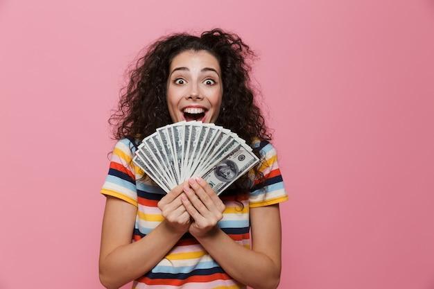 Piękna kobieta w wieku 20 lat z kręconymi włosami trzymająca fana dolarowych pieniędzy na różowo