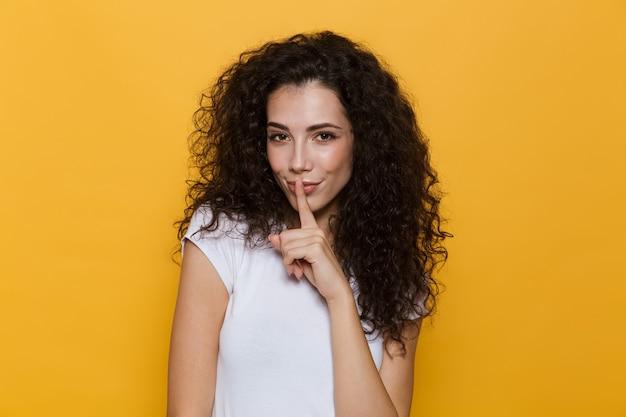 Piękna kobieta w wieku 20 lat z kręconymi włosami trzymająca palec na ustach na żółto