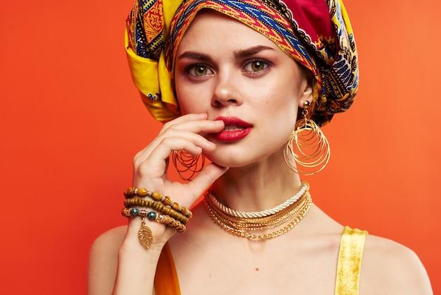 Piękna kobieta w wielobarwnym turbanie atrakcyjny wygląd biżuterii na białym tle