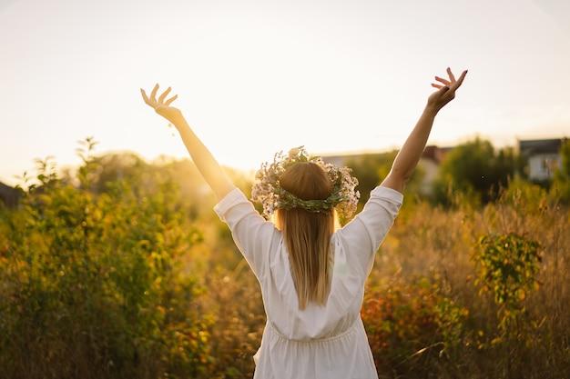 Piękna kobieta w wieńcu z dzikich kwiatów, stojąca z powrotem w kwietnym polu, ręce z boku