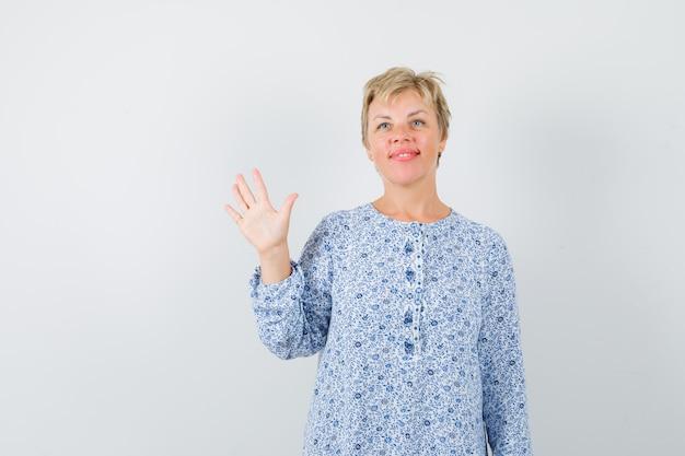 Piękna kobieta w wzorzystej bluzce macha ręką na pożegnanie, widok z przodu.