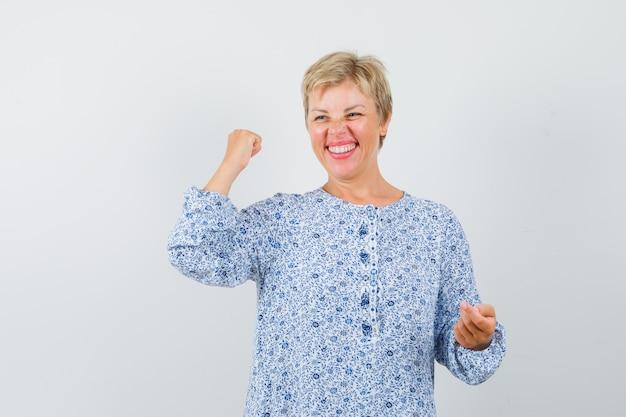 Piękna kobieta w wzorzystej bluzce pokazano jej szczęście, widok z przodu.
