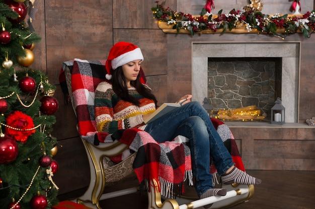 Piękna kobieta w zabawnym świątecznym kapeluszu czytająca siedząc na bujanym fotelu w pobliżu choinki w salonie z udekorowanym kominkiem