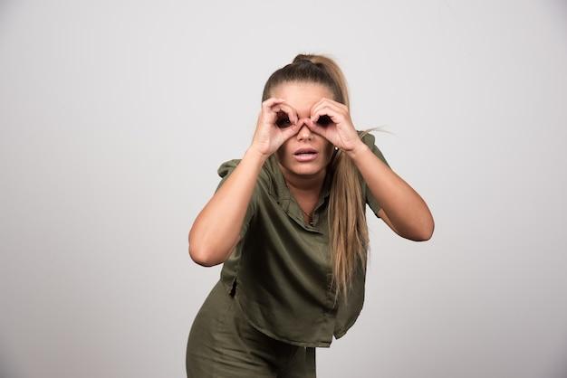 Piękna kobieta w zielonej kurtce patrząc na kamery przez jej ręce.