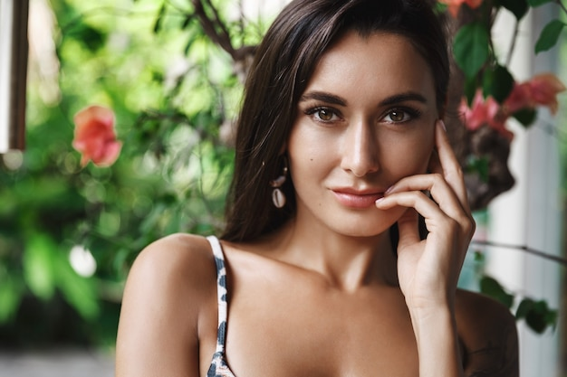 Piękna kobieta w zielonej tropikalnej przyrody, pozowanie w pobliżu liści i kwiatów w bikini.
