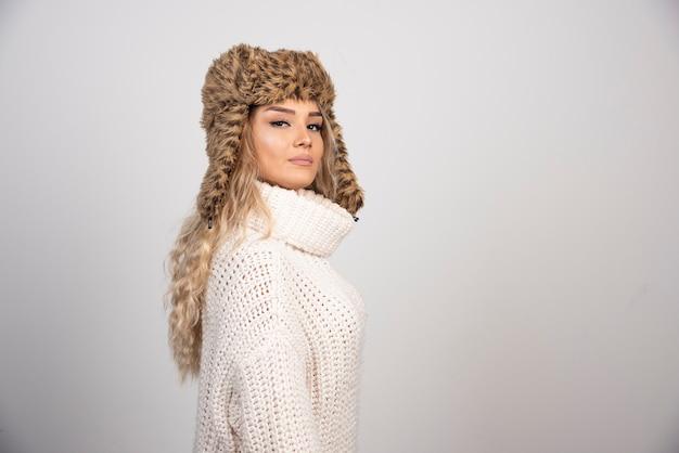 Piękna kobieta w zimowy strój patrząc na kamery.