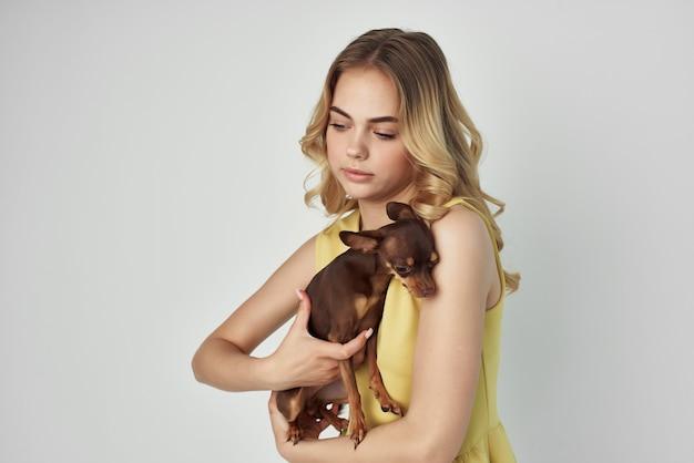 Piękna kobieta w żółtej sukience zabawia się małym psem przyciętym widokiem mody