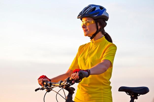 Piękna kobieta w żółtym rowerzysta na rowerze dociera w słońcu
