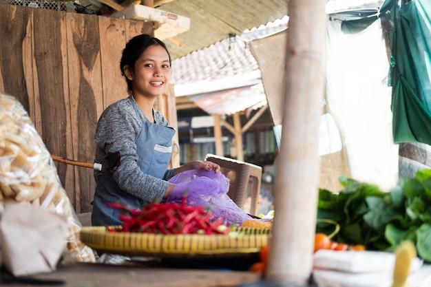 Piękna kobieta warzywniaka uśmiecha się, wyciągając szalotkę z worka na straganie z warzywami