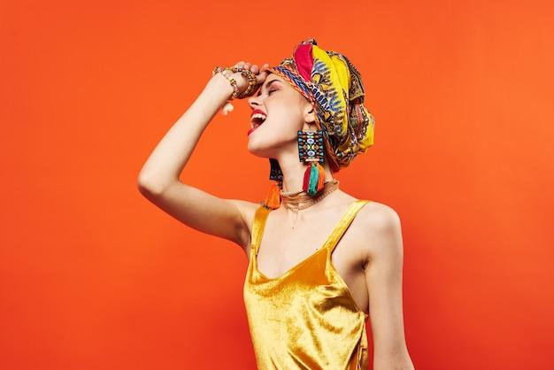 Piękna kobieta wielobarwny szal etniczne afrykańskim stylu dekoracje czerwone tło. zdjęcie wysokiej jakości