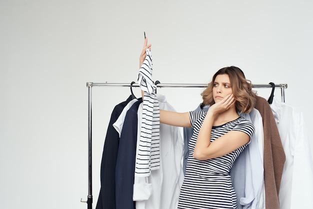 Piękna kobieta wieszak na ubrania zakupy na białym tle