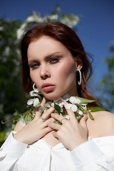 Piękna kobieta wiosną w gałęziach kwitnących krzewów jabłoni