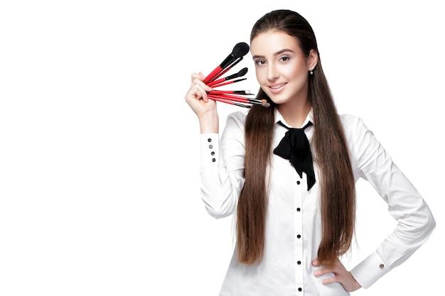 Piękna kobieta wizażystka z naturalnym makijażem trzymająca pędzel do makijażu na białym tle