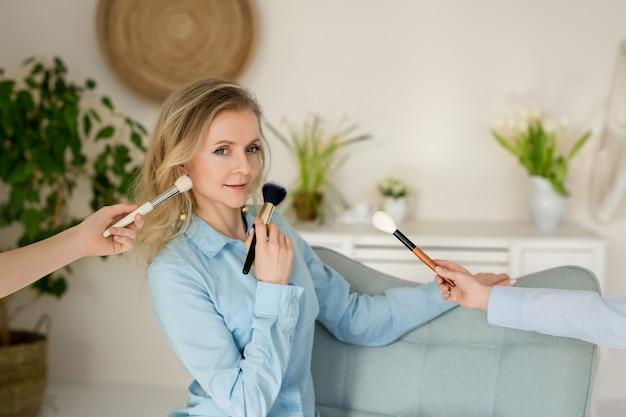 Piękna kobieta wizażystka z pędzlem do makijażu w dłoniach