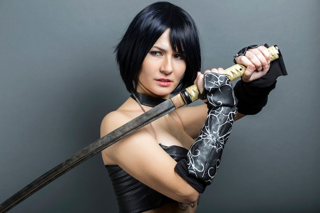 Piękna kobieta-wojownik z mieczem na szarym tle.