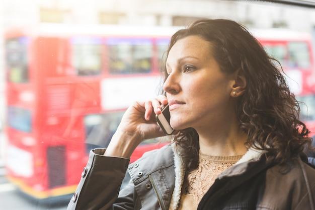 Piękna kobieta, wpisując na inteligentny telefon podczas dojazdów do pracy w londynie