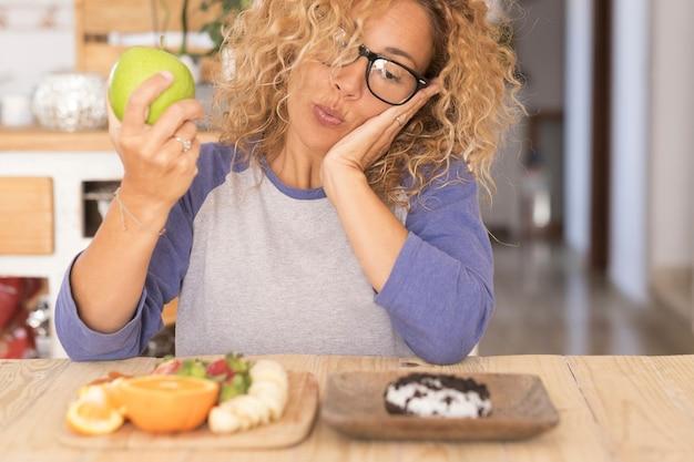 Piękna kobieta wybiera między jabłkiem a innym owocem lub pączkiem - trudno zmienić jej styl życia - 40 lat w okularach patrząc na pączka z jabłkiem w dłoni