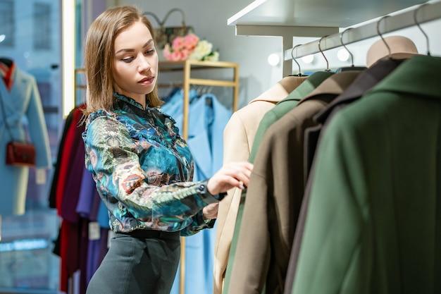 Piękna kobieta wybiera płaszcz w sklepie