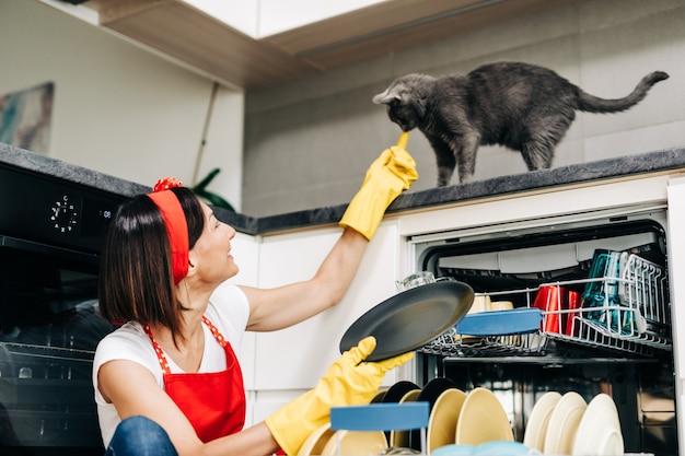 Piękna kobieta wyjmując czyste naczynia ze zmywarki.