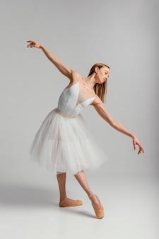 Piękna kobieta wykonuje balet pełny strzał