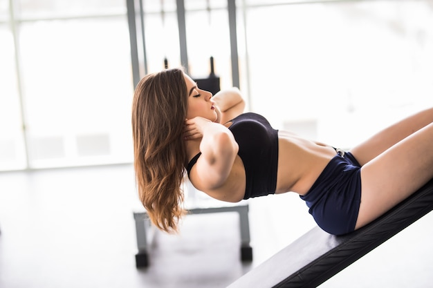 Piękna kobieta wykonuje ćwiczenia prasy na symulatorze sportowym dla swojego sprawnego ciała w nowoczesnej siłowni