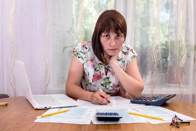 Piękna kobieta, wypełniając formularz 1040 w biurze