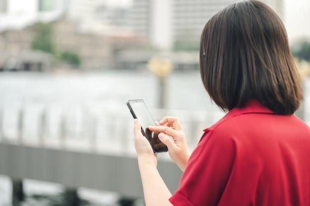 Piękna kobieta z azji używa smartfona w centrum miasta do wyszukiwania różnych