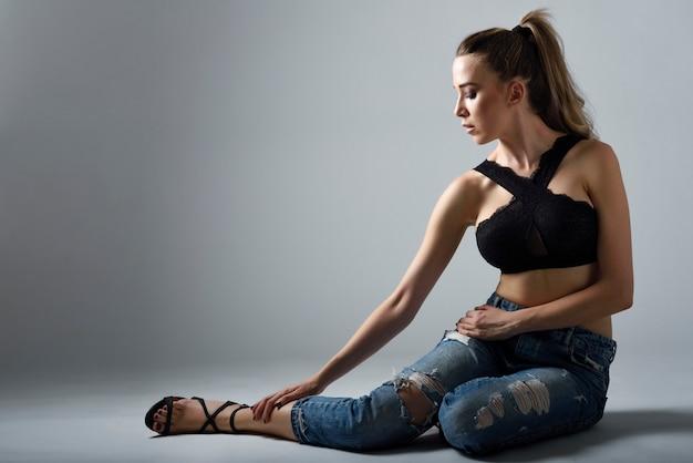 Piękna kobieta z bardzo długimi włosami na sobie czarny stanik i niebieskie dżinsy w pozycji siedzącej
