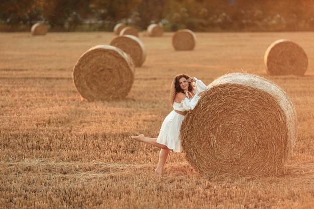 Piękna kobieta z belami słomy latem