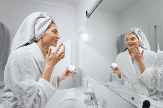 Piękna kobieta z białym ręcznikiem po prysznicu robi makijaż