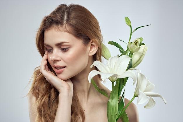Piękna kobieta z białymi kwiatami w dłoniach na białym tle