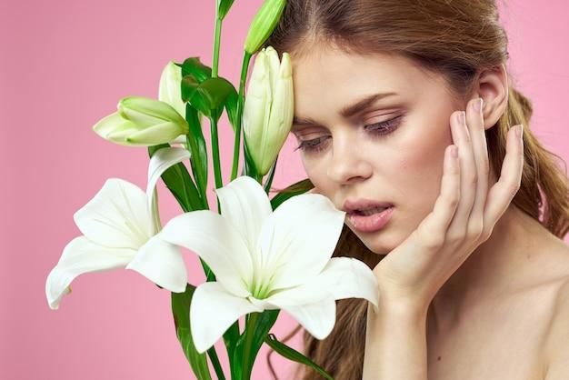Piękna kobieta z białymi kwiatami w dłoniach na różowym tle