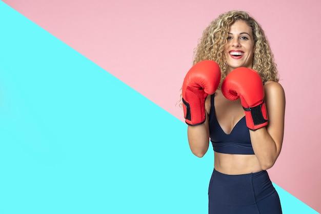 Piękna kobieta z blond kręconymi włosami o ładnym uśmiechu jest szczęśliwa uśmiechnięta i ubrana w sportową boks