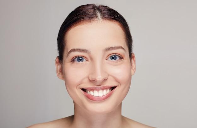 Piękna kobieta z brązowymi włosami, czystą świeżą skórą pozującą na szarym studiu, wyglądająca prosto, szeroko się uśmiechająca, model z lekkim nagim makijażem