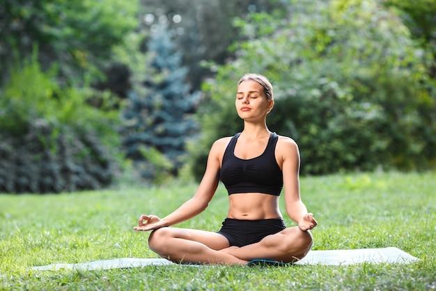 Piękna kobieta z brązowymi włosami na sobie czarny top i spodenki robi pozycję jogi w parku, zdrowy styl życia, portret, medytacja.