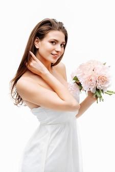 Piękna kobieta z bukietem kwiatów pozuje w białej sukni w studio na białym tle. pionowy portret w studio. koncepcja naturalnego piękna.
