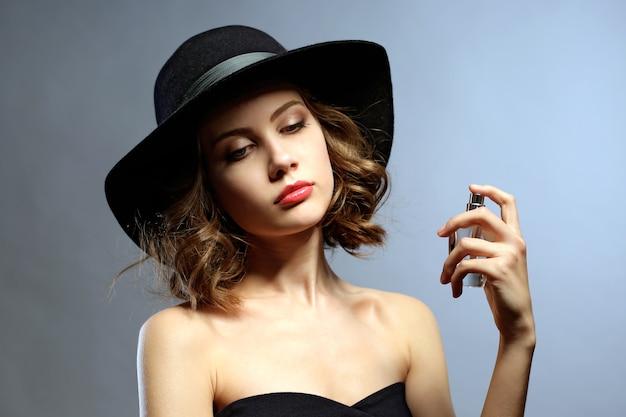 Piękna kobieta z butelką perfum na szaro