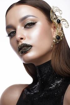 Piękna kobieta z czarnym makijażem sztuki kreatywnej i złotymi akcesoriami