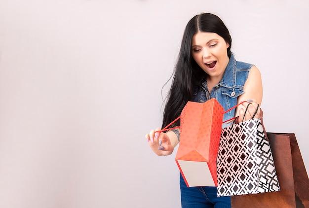 Piękna kobieta z czarnymi włosami, trzymając torby na zakupy na białym tle na białej ścianie