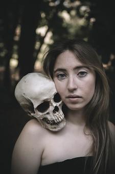 Piękna kobieta z czaszką w lesie