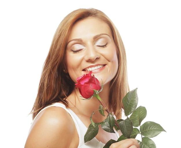 Piękna kobieta z czerwoną różą na białym tle