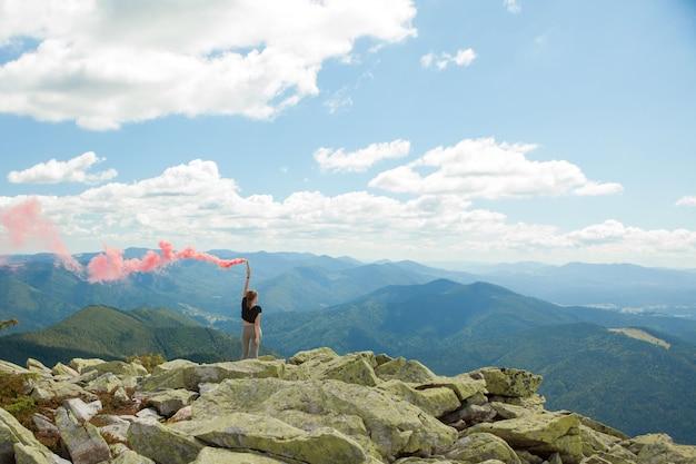 Piękna kobieta z czerwonym kolorowym dymem na szczycie góry i pochmurnego nieba w tle.