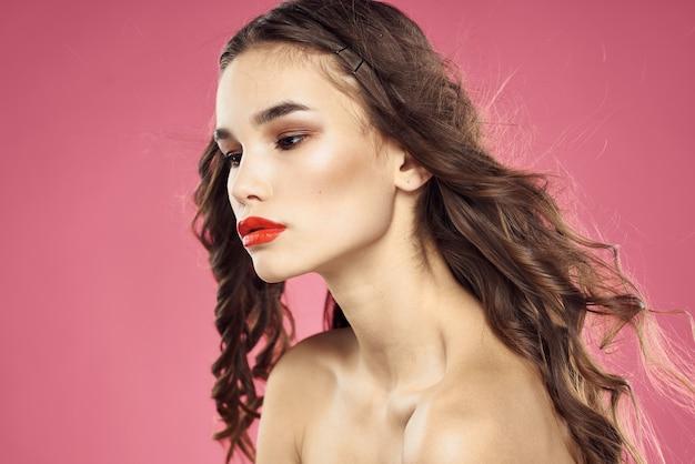 Piękna kobieta z czerwonymi ustami na różowym tle nagie ramiona przycięty widok. wysokiej jakości zdjęcie